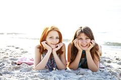Two beautiful girls lie on the beach. Stock Photos