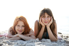 Two beautiful girls lie on the beach. Royalty Free Stock Photography