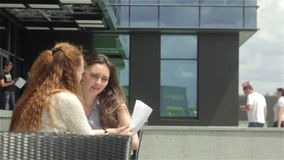 Two beautiful girls looking through business documents in outdoor cafe. Shooting from the back of girl. Two beautiful young women sitting in outdoor cafe near stock video footage