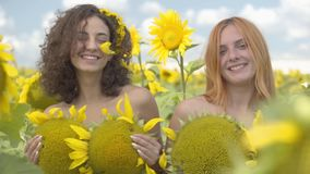 Two beautiful girls looking at the camera smiling standing on the sunflower field covering bodies with sunflowers