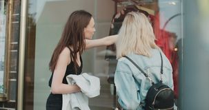 Two beautiful girls looking at clothes in a shop window. Cheerful teenage girls shopping together in a city stock footage