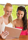 Two beautiful girls looking at tablet pc computer in cafe outside Stock Photography