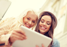Two beautiful girls looking into tablet pc Stock Photography