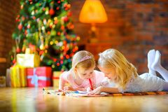 Two beautiful girls are lying on the floor near the Christmas tree and diligently writing a letter royalty free stock images
