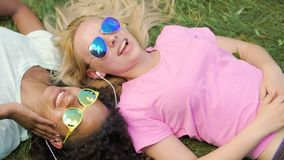 Two beautiful girls lying on grass, listening to music and singing song together. Stock footage stock video footage