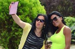 Two beautiful girls make selfi stock image