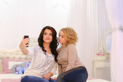 Two beautiful girls make selfie photo, using gadget, for memory, royalty free stock images