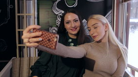 Two beautiful girls make selfie on smartphone in restaurant. stock video footage