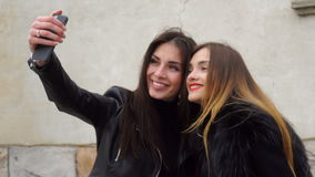 Two beautiful girls makes selfie on the phone. Two beautiful girls photographed on the phone stock video