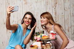 Two beautiful girls making selfie at party. Royalty Free Stock Photo