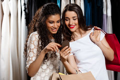 Two beautiful girls making shopping, looking at phone in mall. Two young beautiful girls making shopping, smiling, holding purchases, looking at phone in mall Stock Images