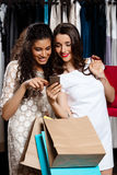 Two beautiful girls making shopping, looking at phone in mall. Two young beautiful girls making shopping, smiling, holding purchases, looking at phone in mall Royalty Free Stock Photos
