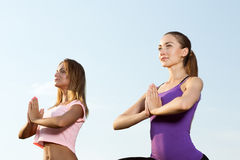 Two beautiful girls meditating outdoors. Two beautiful girls meditating in the park Royalty Free Stock Images