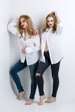 Two beautiful girls in men shirts and jeans royalty free stock photography