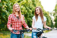 Two beautiful girls near bikes. Young blond beautiful girl and her charming friend standing smiling near their bikes holding the handlebars wearing jeans green Royalty Free Stock Images