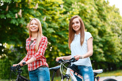 Two beautiful girls near bikes. Young blond beautiful girl and her charming friend standing smiling near their bikes holding the handlebars wearing jeans green Royalty Free Stock Photography