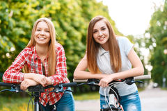Two beautiful girls near bikes. Young beautiful girl with brown hair together with her blond pretty friend standing leaning on the handlebars of their bikes Royalty Free Stock Images