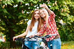Two beautiful girls near bikes. Two young beautiful smiling girls standing together near their bikes making selfie on smartphone in the green park Royalty Free Stock Photography