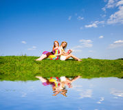 Two beautiful girls with notebook outdoors. Sitting on the green grass near water Stock Photography