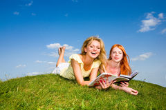 Two beautiful girls with notebooks outdoors. Lay on the green grass. Against the backdrop of blue sky Royalty Free Stock Images