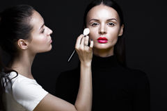 Two beautiful girls on photo shoot to apply face makeup . Beauty fashion model. stock images