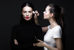 Two beautiful girls on photo shoot to apply face makeup . Beauty fashion model. Two beautiful girls on a photo shoot to apply makeup to the face. Beauty fashion Royalty Free Stock Photos