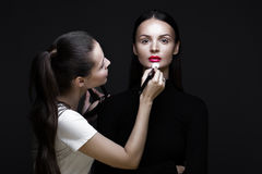 Two beautiful girls on photo shoot to apply face makeup . Beauty fashion model. royalty free stock photos