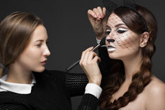 Two beautiful girls on photo shoot to apply face makeup . Beauty fashion model. Royalty Free Stock Photo
