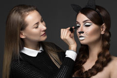 Two beautiful girls on photo shoot to apply face makeup . Beauty fashion model. Stock Photo