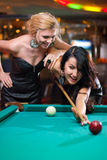 Two beautiful girls are playing billiards Royalty Free Stock Photography
