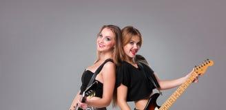 Two beautiful girls playing guitars Royalty Free Stock Image