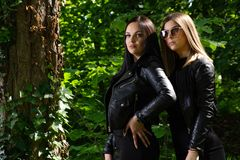 Two beautiful girls posing in a forest on a sunny spring day. The girl wears a black dress and a leather jacket. Forest in background. Fashionable cute female stock image