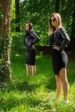 Two beautiful girls posing in a forest on a sunny spring day. The girl wears a black dress and a leather jacket. One girl is in focus. Forest in background stock photos