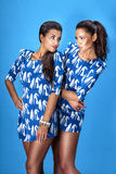 Two beautiful girls posing over blue background. Royalty Free Stock Photos