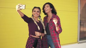 Two beautiful girls posing to take selfie. Beautiful girls taking photos with smart phone standing by the yellow wall. Slowmotion shot stock video footage