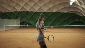 Two beautiful girls practicing. The handicapped girl in short shorts takes the ball from the basket and makes the first. Serve of the ball. Indoor tennis court stock video