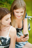 Two beautiful girls read sms Stock Photos