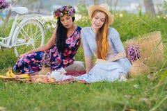 Two girls reading book, enjoying picnic. Two beautiful girls reading book, enjoying picnic Stock Images
