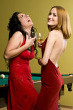 Two beautiful girls in red with cognac Royalty Free Stock Photography