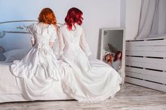 Two beautiful girls with red hair in a beautiful white wedding Victorian dresses. Female style. The fragile girl. Thin waist. Two women sitting in the bedroom stock images