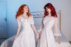 Two beautiful girls with red hair in a beautiful white wedding Victorian dresses Stock Images