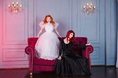 Two beautiful girls with red hair in a beautiful white wedding Victorian dresses. Two girls with red hair in retro dress in the bedroom. Femme fatale in a black Royalty Free Stock Images
