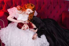 Two beautiful girls with red hair in a beautiful white wedding Victorian dresses. Two girls with red hair in retro dress in the bedroom. Femme fatale in a black Royalty Free Stock Photography