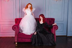 Two beautiful girls with red hair in a beautiful white wedding Victorian dresses. Two girls with red hair in retro dress in the bedroom. Femme fatale in a black Royalty Free Stock Image