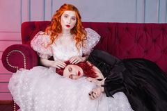 Two beautiful girls with red hair in a beautiful white wedding Victorian dresses. Two girls with red hair in retro dress in the bedroom. Femme fatale in a black Stock Images