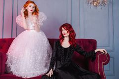 Two beautiful girls with red hair in a beautiful white wedding Victorian dresses. Two girls with red hair in retro dress in the bedroom. Femme fatale in a black Stock Photography
