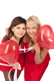 Two beautiful girls with red heart balloon Royalty Free Stock Image