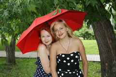 Two beautiful girls with red umbrella in park Stock Photo