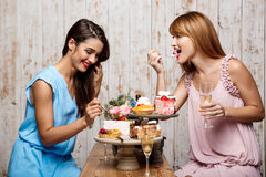 Two beautiful girls resting at party. Two young beautiful girls in dresses eating cakes, smiling, laughing, drinking champagne, resting at party Stock Image
