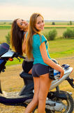 Two beautiful girls resting after riding scooter. On sunny summer day Stock Photos